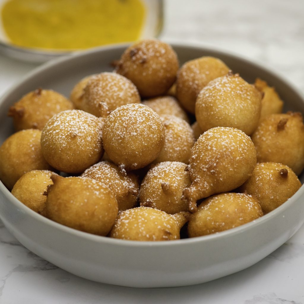 African beignets (puff puff) in a grey bowl with mango sauce to the side