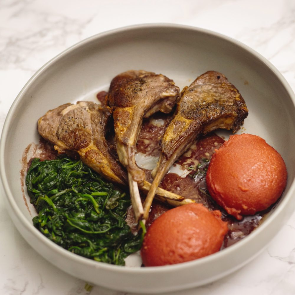 Red fufu with lamb chops and sautéed spinach